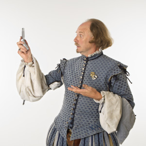 William Shakespeare in period clothing looking at cell phone with astonishment.