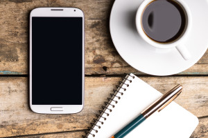 Smartphone with notebook and cup of strong coffee on wooden background. Cell phone with writing set with espresso
